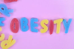 Obesity word on pink table Royalty Free Stock Photography