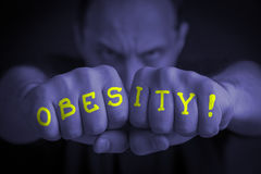 OBESITY written on an angry man's fists. OBESITY written on the fingers of an angry man's fists. Blue colored. Message concept image Royalty Free Stock Images