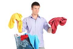 Obeslutsam man som rymmer två tröjor Arkivfoto