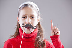 Obey to my moustaches, people!. Little girl with fake mustache laying down the law being stuck up stock photography