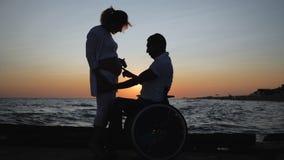 Obezwładniający w wózku inwalidzkim słucha podbrzusze jego żona w wieczór, kalecząca miłość, ciężarna kobieta z nieważnym mężem zbiory wideo