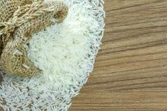 Obfitość jaśminowi ryż w worku, na drewnianym tekstury tle z bezpłatną przestrzenią Obrazy Stock