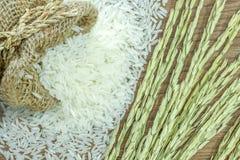Obfitość jaśminowi ryż w worku z ucho ryż, na drewnianym tekstury tle Zdjęcia Stock