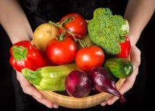 Obfitość mokrzy warzywa w drewnianym naczyniu na kobiet rękach zdjęcie royalty free