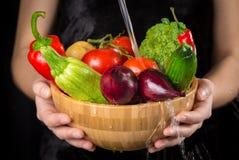 Obfitość mokrzy warzywa w drewnianym naczyniu na kobiet rękach zdjęcia royalty free