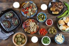 Obiadowy stół z mięsnym grillem, bbq warzywami, sałatkami, kumberlandami, przekąskami i piwem, odgórny widok Obraz Royalty Free