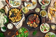 Obiadowy stół z mięsnym grillem, pieczone nowe grule, różny jedzenie zdjęcie royalty free