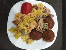 Obiadowy talerz z kolorowym makaronem, klopsikami i pomidorem, na białym talerzu zdjęcie royalty free