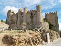 Obidos Castle Portugal. View of Obidos Castle in Portugal against a blue sky with clouds royalty free stock images