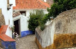 Beautiful tiny cobblestoned street, walls, and roofs in Obidos, Portugal stock images