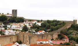 Obidos in Portugal. The old city is surrounded by walls and towers still intact. Along the various roads of the city there are houses with white edges in green Stock Photos