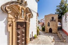 Obidos, Portugal Portal da igreja de Misericordia e a sinagoga medieval de Sephardic no fundo fotos de stock royalty free