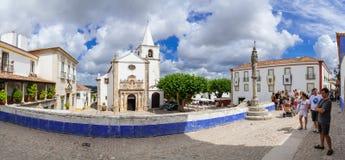 Obidos, Portugal. Santa Maria Church and Town Pillory seen from Direita Street. Stock Photo