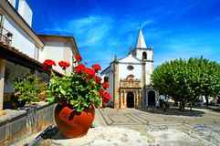 Obidos town Portugal. Low angle view of church in Obidos town with pot of colorful red flowers in foreground, Portugal Stock Photography