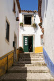 Obidos village Portugal. Narrow steep street and white walls  in old Medieval Obidos village in Portugal Stock Photo