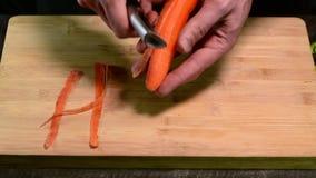 Obieranie marchewka z obieraczką na drewnianej desce zbiory