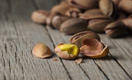 Obieranie pistacja w nutshell na drewnianym nieociosanym tle fotografia stock