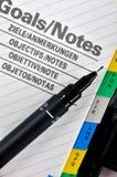 Obiettivi e pagina della nota con la penna Fotografie Stock