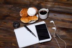 Obiettivo con i croissant ed il caffè accanto al taccuino fotografia stock