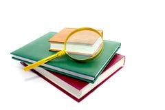 Obiettivo del Magnifier e mucchio dei libri Fotografie Stock