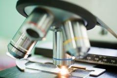 Obiettivo del microscopio con la striscia blu sul campione Fotografia Stock Libera da Diritti