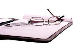 Obiettivo, libro e penna con priorità bassa bianca fotografie stock