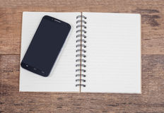 Obile phone and book note in vintage wooden Royalty Free Stock Photography