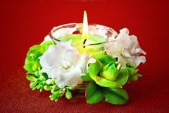 Candle and flowers. On a red background Royalty Free Stock Photos