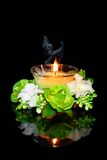 Candle and flowers on a black background. Burning candle on a black background Stock Images
