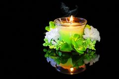 Candle and flowers on a black background. Burning candle on a black background Royalty Free Stock Image