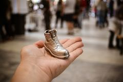 Object in the form of a boot printed on a 3d printer and covered with enamel. On hand close-up. On the back of a blurry plan - people. Progressive modern royalty free stock images