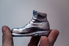 Object in the form of a boot printed on a 3d printer and covered with enamel. On hand close-up. Progressive modern additive technology. Copy spase Stock Images