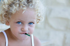Object in mouth. Young caucasian child with a dangerous small object in her mouth which is a choking hazard royalty free stock photo