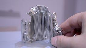 Object printed on metal 3d printer. Dental crowns printed in laser sintering machine. Modern 3D printer printing from metal powder. Concept progressive stock footage