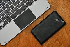 Objecte les mensonges de smartphone l'appareil-photo et une pièce du clavier avec le touchpad sur un fond en bois photo stock