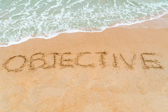 OBJECTIVE inscription written on sandy beach with wave approachi Royalty Free Stock Photo