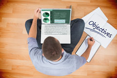 Objectives  against young creative businessman working on laptop Royalty Free Stock Image