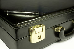 Objects of a businessman. Briefcase in black leather with pen Royalty Free Stock Images