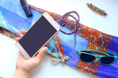 Objects of female life on a white table, phone, brooch, color scarf Stock Photo