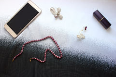 Objects of female life on a white table, phone, brooch Stock Photos