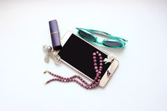 Objects of female life on a white table, phone, brooch Royalty Free Stock Image