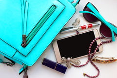 Objects of female life on a white table, phone, brooch, lipstick, glasses, beads, hair pin Royalty Free Stock Photography