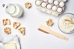 Objects and ingredients for baking, plastic molds for cookies on a white background. Flour, eggs, milk, butter, cream. Top view, space for text. Still life Royalty Free Stock Images