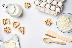 Objects and ingredients for baking, plastic molds for cookies on a white background. Flour, eggs, milk, butter, cream. Top view, space for text. Still life Royalty Free Stock Photo