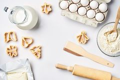 Objects and ingredients for baking, plastic molds for cookies on a white background. Flour, eggs, rolling pin, milk. Butter, cream. Top view, space for text Stock Photos