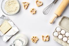 Objects and ingredients for baking, plastic molds for cookies on a white background. Flour, eggs, rolling pin, whisk. Milk, butter, cream. Top view, space for Stock Photo