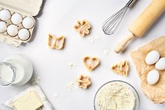 Objects and ingredients for baking, plastic molds for cookies on a white background. Flour, eggs, rolling pin, whisk. Milk, butter, cream. Top view, space for Royalty Free Stock Photo