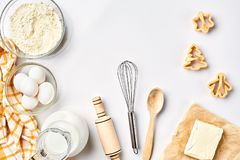 Objects and ingredients for baking, plastic molds for cookies on a white background. Flour, eggs, rolling pin, whisk. Milk, butter, cream. Top view, space for Stock Photography