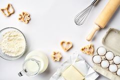 Objects and ingredients for baking, plastic molds for cookies on a white background. Flour, eggs, rolling pin, whisk. Milk, butter, cream. Top view, space for Royalty Free Stock Photography