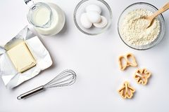 Objects and ingredients for baking, plastic molds for cookies on a white background. Flour, eggs, whisk, milk, butter. Cream. Top view, space for text. Still Royalty Free Stock Photography